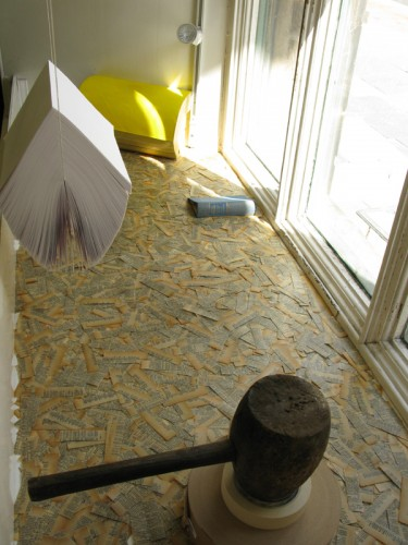 untitled 2010 (installation made out of various materials, among them: cut pages dipped in beeswax, old dictionary, old phone book, printing paper stacked - suspended, mallet, rolls of tape. dimensions vary, trapezium size of the windowsill 128 x 63 x 163 cm )