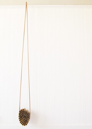 """""""Suspension"""" 2010 (rolled pages of the book entitled """"Field events: Technique, Strategy and Training"""" (London 1953), beeswax, shuttlecock crowns, gum tape. 304 x 28 x 13 cm)"""