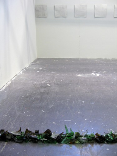 """""""Pigeon-hole"""" 2008: Installation of 12 etchings, grey painted wall, broken bottles."""